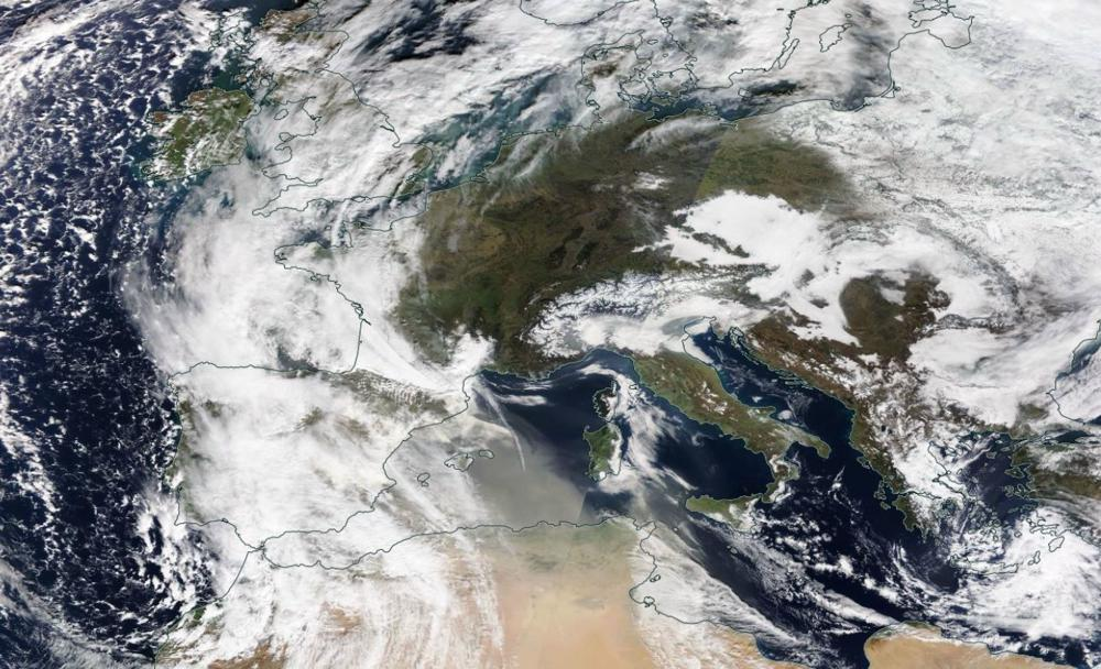 Satellietbeeld met gelige Saharastof rondom de Balearen. (Bron: NASA)